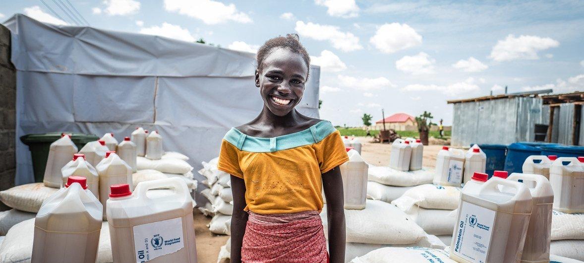 Une jeune fille nigériane sourit après avoir reçu de l'aide alimentaire. Plus de 5 millions de personnes au Nigéria sont confrontées à la faim.