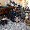 一位流离失所的叙利亚母亲从东古塔的枪林弹雨中逃出,正在大马士革郊区的一个集体安置点里用柴火和一些硬纸板为她的孩子烹煮鸡蛋。