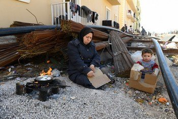 أرشيف: أم سورية وطفلها، من النازحين من الغوطة الشرقية في سوريا. تستخدم حطب الوقود وبعض الورق المقوى لغلي البيض في ملجأ في ريف دمشق.