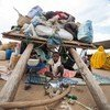 This woman and her child sheltered under their cart are among thousands who have fled violence and are now in Al Salam camp for Internally Displaced Persons, South Darfur. (file)