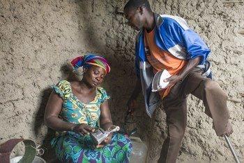 Adeline Hatangimana (kushoto)  mwenye umri wa miaka 30 ambaye alipoteza jicho moja akiwa mtoto nchini Burundi, akirebisha pasi ya mkaa waliyotengeneza kwa kutumia chuma chakavu katika karakana yao kambini Lusenda, DRC.