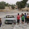 En Al Tabqa, Siria, un grupo de niños pasan al lado de un coche destruido. Más de 850.000 niños siguen viviendo en zonas sitiadas de Siria.
