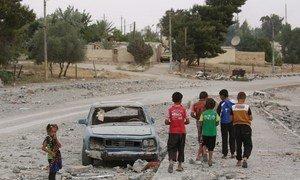 A Al-Taqba, en Syrie, des enfants déracinés par le conflit passent devant une voiture détruite.