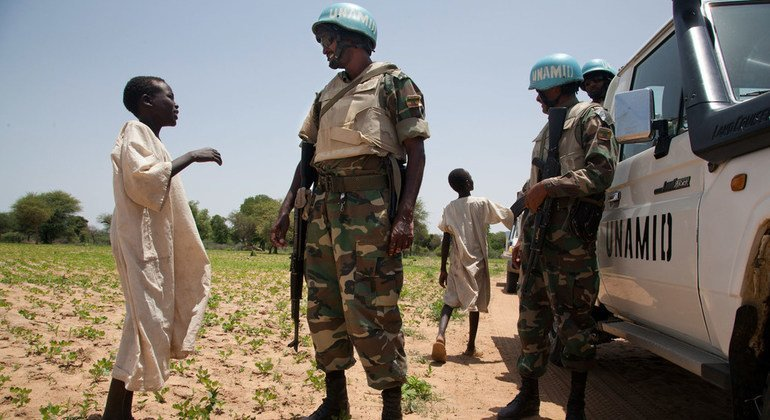 The two boys seen here are chatting with UNAMID peacekeepers from Ethiopia in the volatile Gereida area of South Darfur in July 2012.