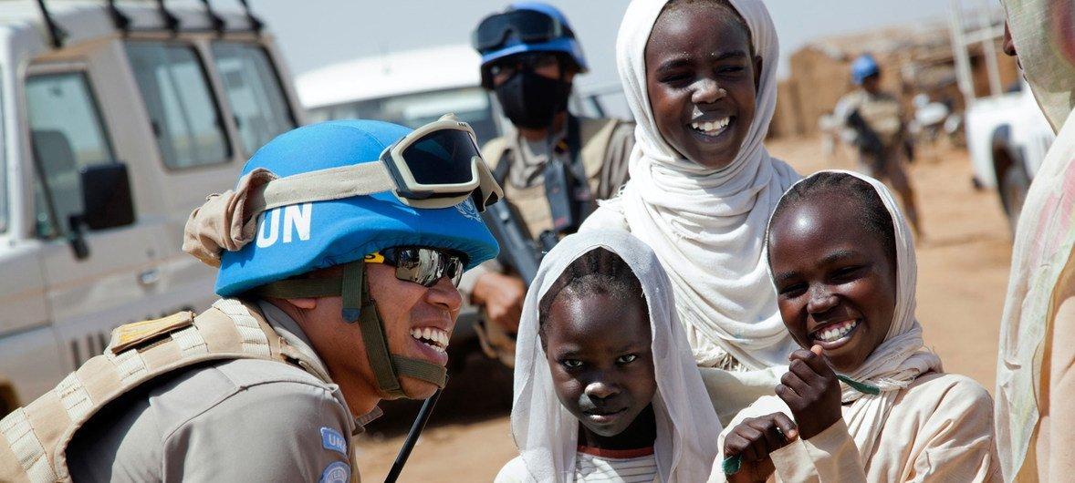 La teniente primera Sigit Jatmiko, miembro de la unidad de policía constituida de la Operación Híbrida de la Unión Africana y las Naciones Unidas en Darfur, habla con varios niños en el campamento de desplazados Abu Shouk durante una patrulla.