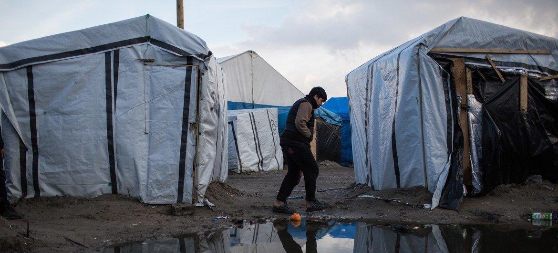 Menino caminha por um acampamento de migrantes em Calais, norte da França