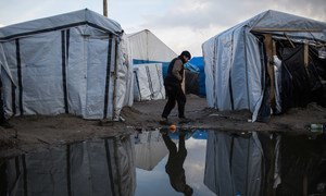 A boy walks through a migrant camp in Calais, northern France. According to estimates, about 900 migrants and asylum seekers are sheltering in the area, many without toilets or washing facilities.