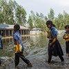 孟加拉国每年都会发洪水,图为2014年9月9日发生洪灾后,学生们上学的路上。2020年季风季节,该国的洪水异常严重。
