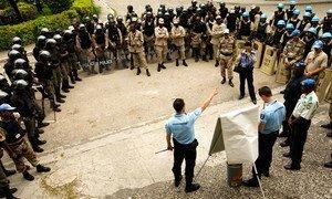 Des policiers de l'ONU originaires de France et du Pakistan se préparent à mener un exercice de contrôle des foules avec des membres de la police nationale haïtienne en avril 2008.