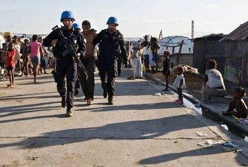 Des Casques bleus français escortent un détenu d'un camp de personnes déplacées en Haïti lors d'une opération de sécurité menée par des militaires et des policiers de l'ONU avec la police nationale haïtienne en juin 2010.