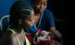 21-year-old Bendu takes her newborn daughter from a midwife at the UNFPA-supported Sinje Health Centre in Liberia.