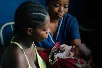 Bendu, âgée de 21 ans, prend son nouveau-né des bras d'une sage-femme au Libéria.