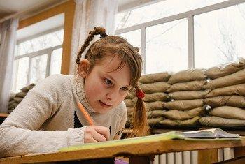 Из-за конфликта на востоке Украины дети вынуждены учиться в школах, окна которых заставлены мешками с песком - это защищает их от обстрелов