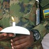 A Rwandan peacekeeper at the UN Mission in South Sudan holds a candle during an April 2017 event to pay tribute to those who perished during the 1994 genocide in Rwanda.