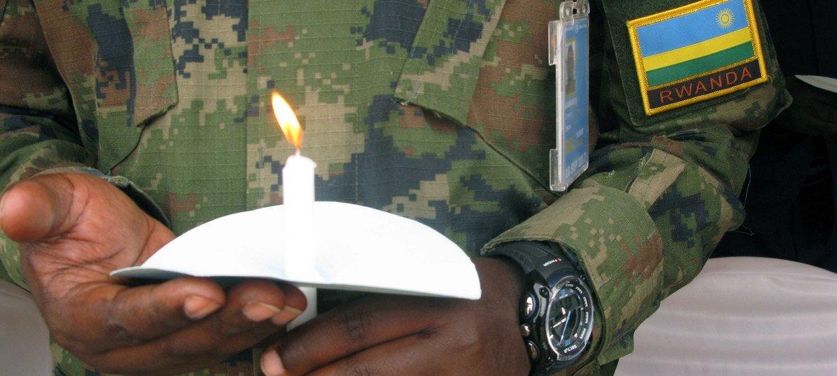 Soldado da paz segura vela em memória das vítimas do genocídio de 1994 no Ruanda.