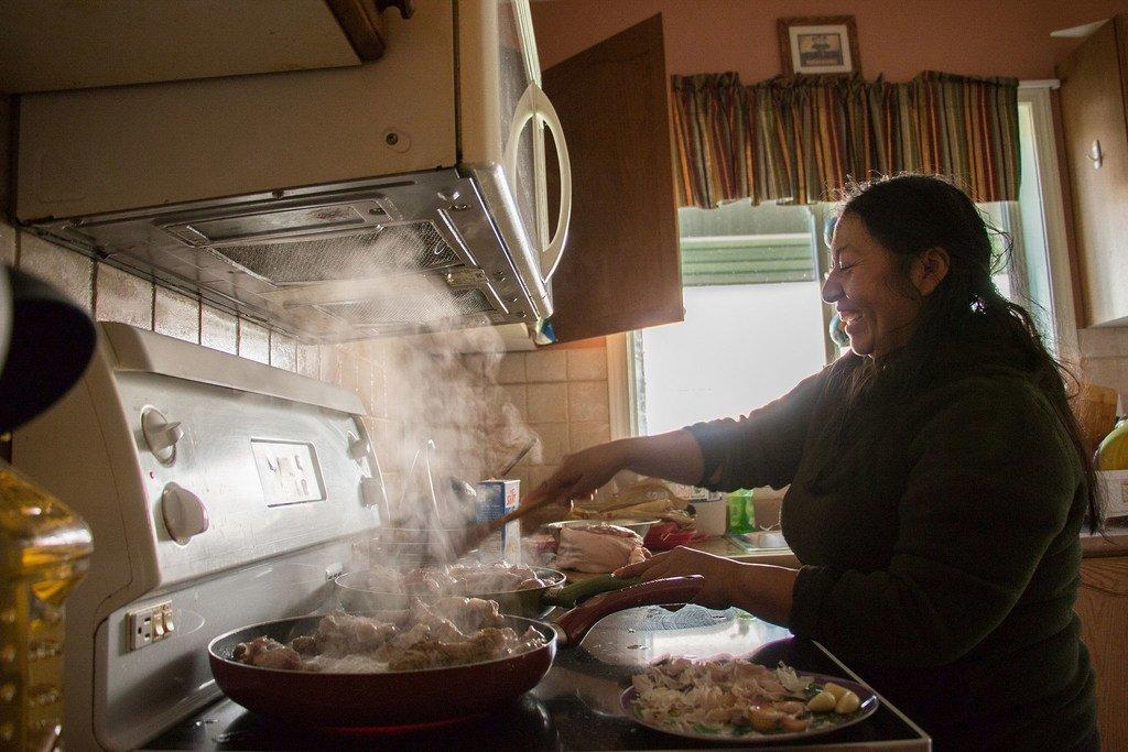 امرأة من السكان الأصليين من أوتافالو، الإكوادور، تطهو في المنزل.
