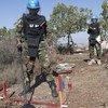 عنصر كمبودي من فريق اليونيفيل لنزع الألغام يزيل النباتات بدقّة من منطقة فيها خطر ألغام بالقرب من رميش.