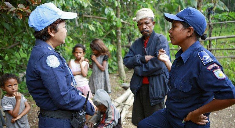 一名来自泰国的联合国警察(左)与一名东帝汶国家警察正在讨论一起案件。