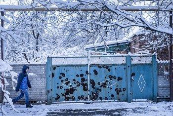 一名儿童走过乌克兰东部顿涅茨克一栋被炮弹损毁的房屋。