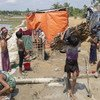 一个罗兴亚男孩扛着一堆柴火,其他难民则在考克斯巴扎难民营内的一口管井边洗澡。这一区域就在涨潮时的水位线上,非常靠近大海,极易受到暴风雨威胁。