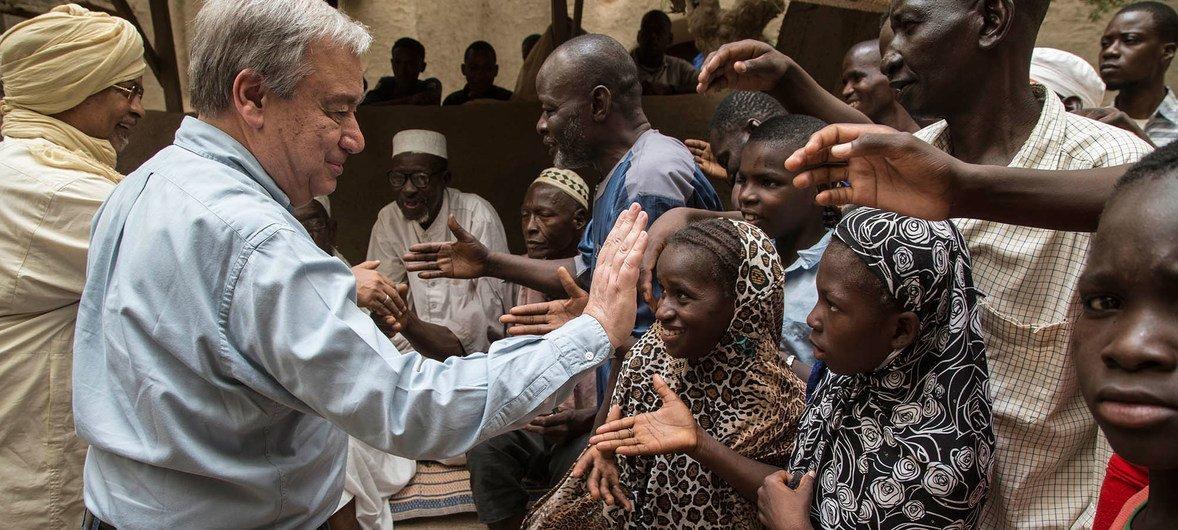 Le Secrétaire général de l'ONU António Guterres est salué par des Maliens après sa visite à la Grande Mosquée de Mopti au Mali.