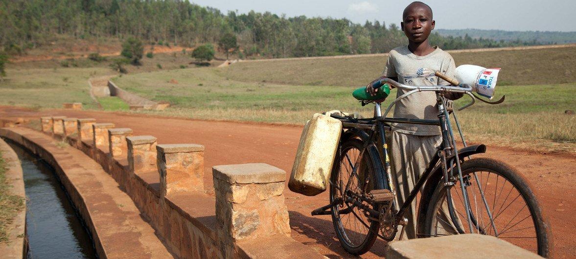Criança com sua bicicleta em Ruanda.