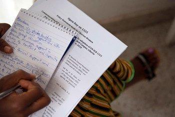 Une jeune femme du Libéria prend des notes lors d'une réunion en 2010 centrée sur les femmes, la paix et la sécurité.