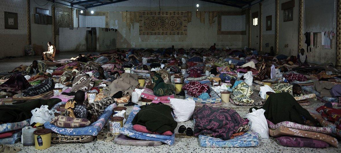 أرشيف: مهاجرون يفترشون الأرض في أحد مراكز الاحتجاز في ليبيا.