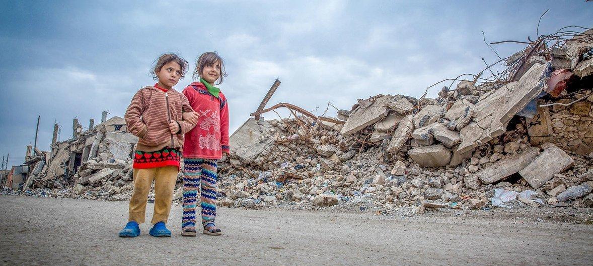 Noor na Sarah wakitembea magharibi mwa Mosul ambako majengo mengi yaliharibiwa.