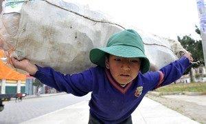Jeune garçon portant des bouteilles de plastique à La Paz, Bolivie