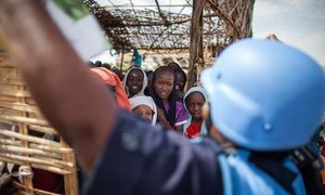 A UNMID police officer speaks with children at a school run inside a camp for internally displaced persons.