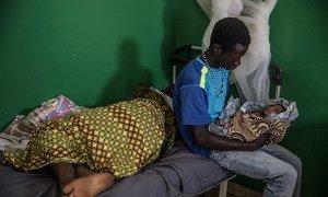 Un joven cuida a su hijo recién nacido en Guinea-Bissau.