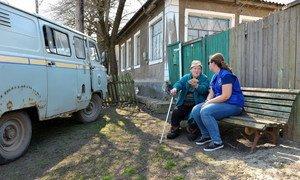 Пожилая жительница получает денежную помощь от Международной организации по миграции (МОМ). Село Крымское, Луганская область, Украина