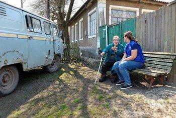 在受冲突影响严重的克里姆斯克(Krymske),国际移民组织工作人员向一位老人提供资金援助。