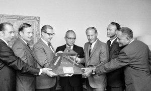 Pichani ni  wataalamu watatu, Armstrong , (wa pili kushoto), Aldrin, (wa tatu kulia) na Collins, (wa pili kulia) wanatembelea makao makuu ya Umoja wa Mataifa, na Katibu Mkuu U Thant (katikati) akiwa na jiwe kutoka mwezini na bendera (Julai 1970) .
