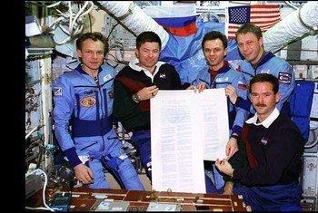 Российские и американские астронавты из экипажа программы «Мир-Шаттл» демонстрирует экземпляр Договора о космосе