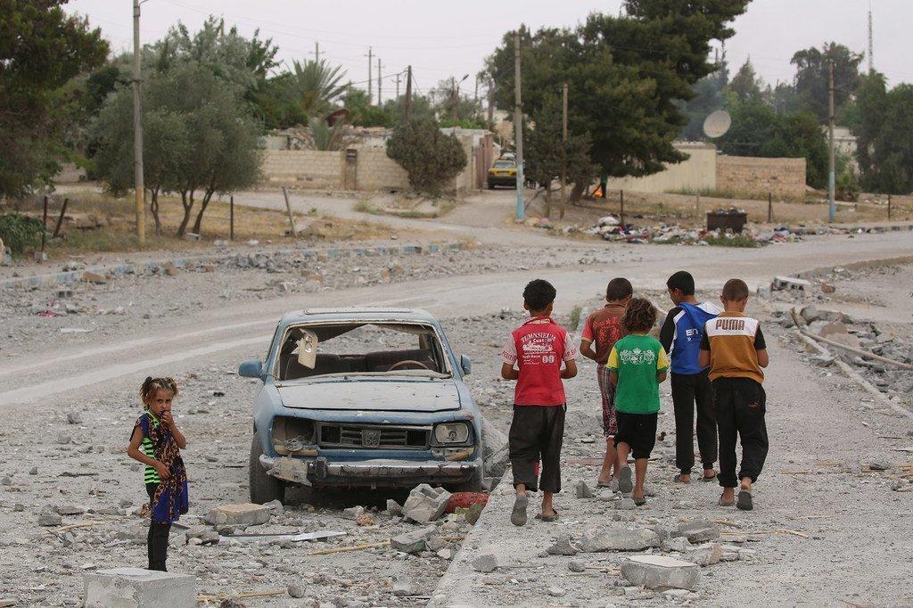 穿着红色T恤的12岁叙利亚儿童哈桑(左二)与朋友们走过一辆被炸毁的汽车。哈桑一家已经两次为躲避暴力而逃离家园,使得他被迫从小学三年级辍学。