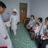 Um médico pediatra, Ri, com crianças no hospital de Jongju, na Coreia do Norte, em maio de 2018.