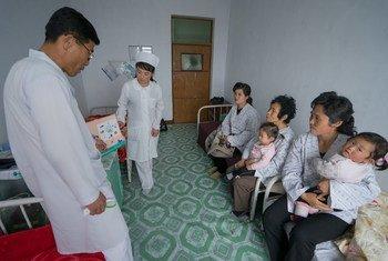 朝鲜的一名儿科医生正就儿童健康问题向面前的几位母亲提供咨询建议。