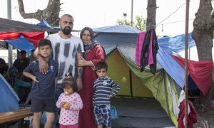 Youssef, a Kurdish-Iraqi from the city of Zakho, stands with his wife and kids outside their small tent in the Diavata reception site near Thessaloniki in northern Greece.