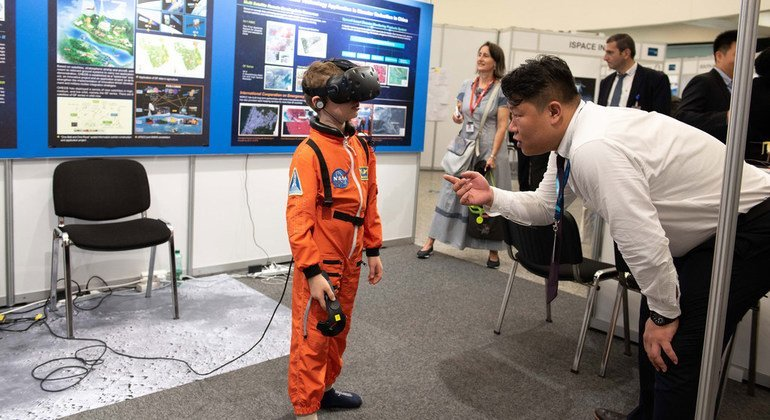 A child in a astronaut suit experiences the moon in a 360 virtual reality at the Chinese Lunar Exploration Programme exhibit.