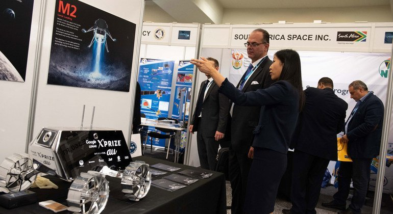 """At the ispace exhibit, an exhibitor explains the MOON VALLEY concept, where Earth and Moon become """"one system""""."""