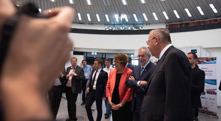 """Austrian President Alexander Van der Bellen (centre), UN Office at Vienna Director-General Yury Fedetov (right), and UNOOSA Director Simonetta Di Pippo (left) look at the UNOOSA exhibit """"Space at the United Nations:1958–2018""""."""