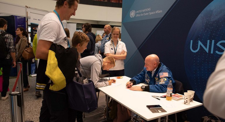 UN Champion for Space Scott Kelly signs autographs and interacts with children at the UNISPACE+50 exhibition.