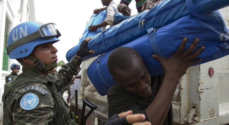 Brazilian United Nations peacekeepers distribute tarps and tents in down town Port au Prince Haiti.