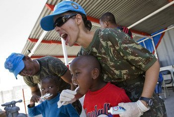 Los miembros del batallón brasileño de la Misión de Estabilización de las Naciones Unidas en Haití (MINUSTAH) enseñan a un grupo de niños locales la atención dental adecuada.