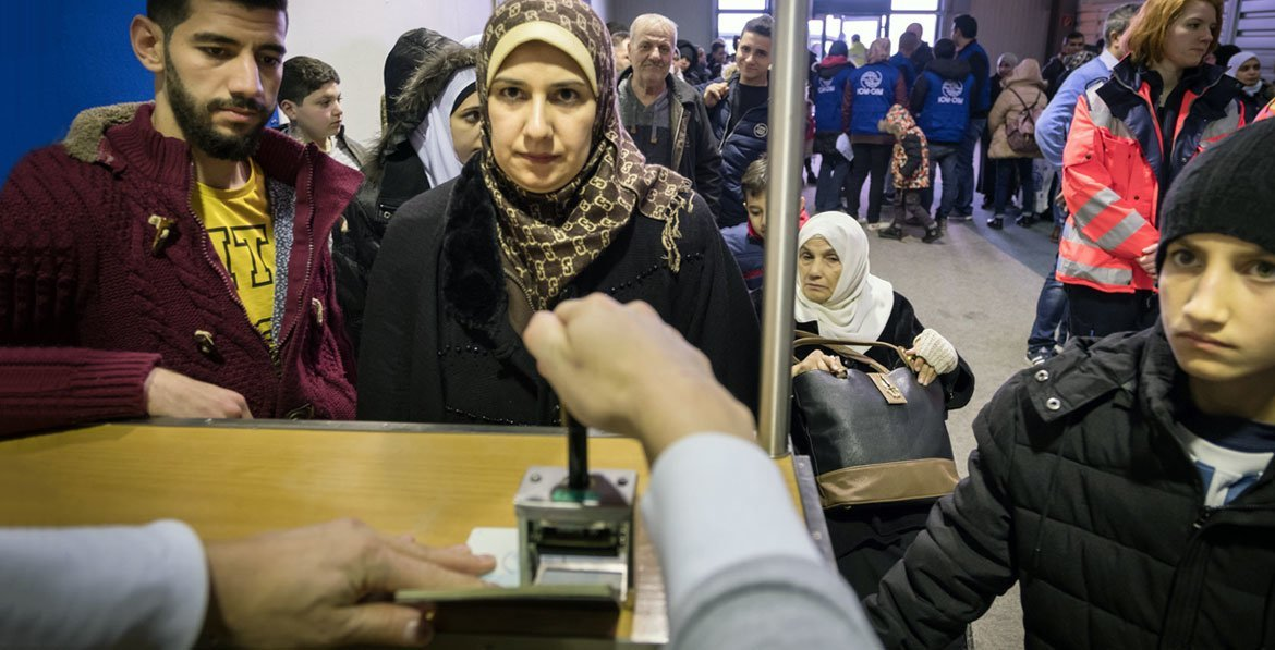 In Germany, a UN resettlement programme gives families hope. Here, an immigration officer stamps the passports of a Syrian family that has just landed at Hanover airport on a charter flight from Egypt.