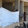 In this file photo, a woman ties a tarpaulin to use as a makeshift wall in an abandoned building in Dara'a, Syria. Recent intensification in fighting has displaced an estimated 330,000 from the region.