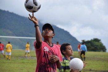 Los niños ven cómo varios excombatientes de las FARC-EP, antiguos paramilitares, miembros de las fuerzas de seguridad, artesanos y jugadores profesionales jugaron un amistoso con la comunidad local de Llano Grande, en el departamento de Antioquia.