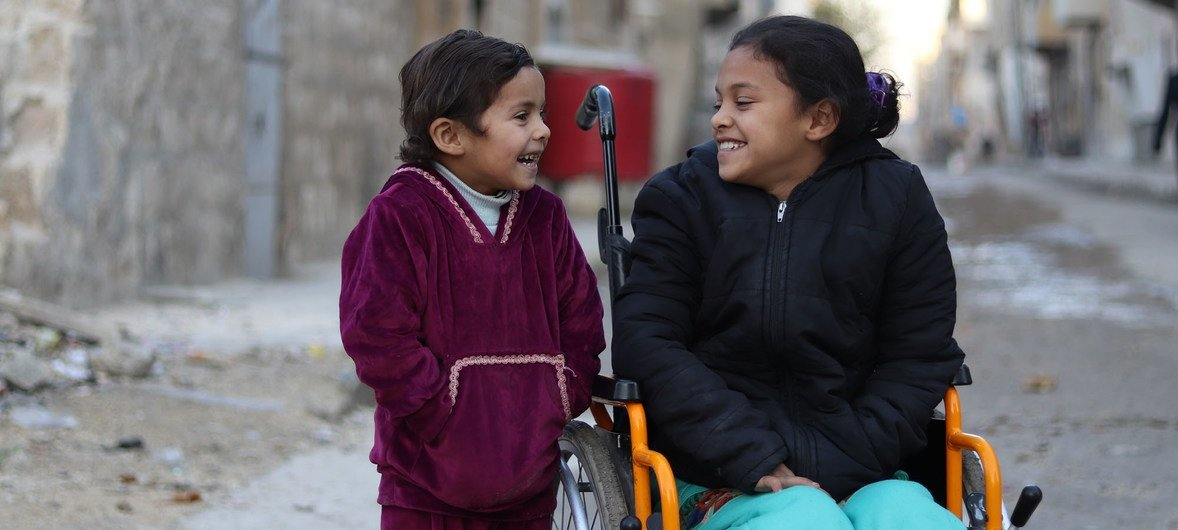 An eight-year-old girl, who was paralysed by an exploding bomb and lost the use of her legs, sits in a wheelchair next to her 5 year old sister, near their home in east Aleppo, Syrian Arab Republic. 11 December 2017.